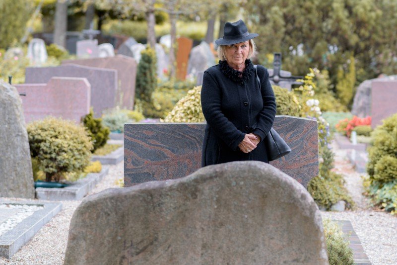 Senior lady in mourning at a graveside standing dressed in full black paying her respects to a departed loved one in a large graveyard