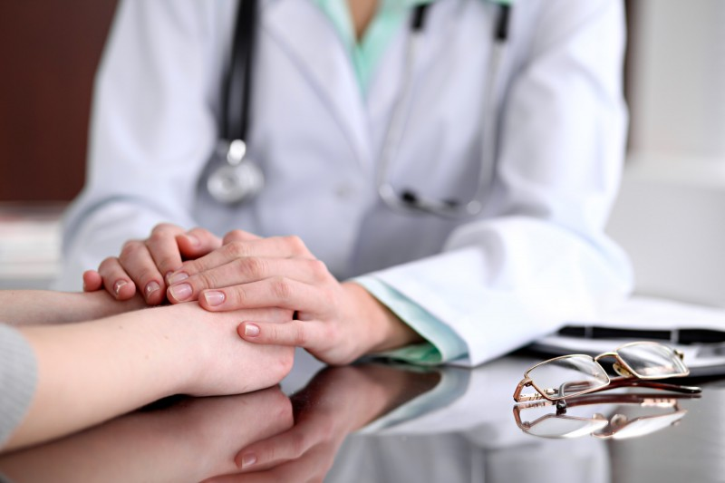 Friendly female doctor hands holding patient hand sitting at the desk for encouragement, empathy, cheering and support while medical examination. Bad news lessening, compassion, trust and ethics concept